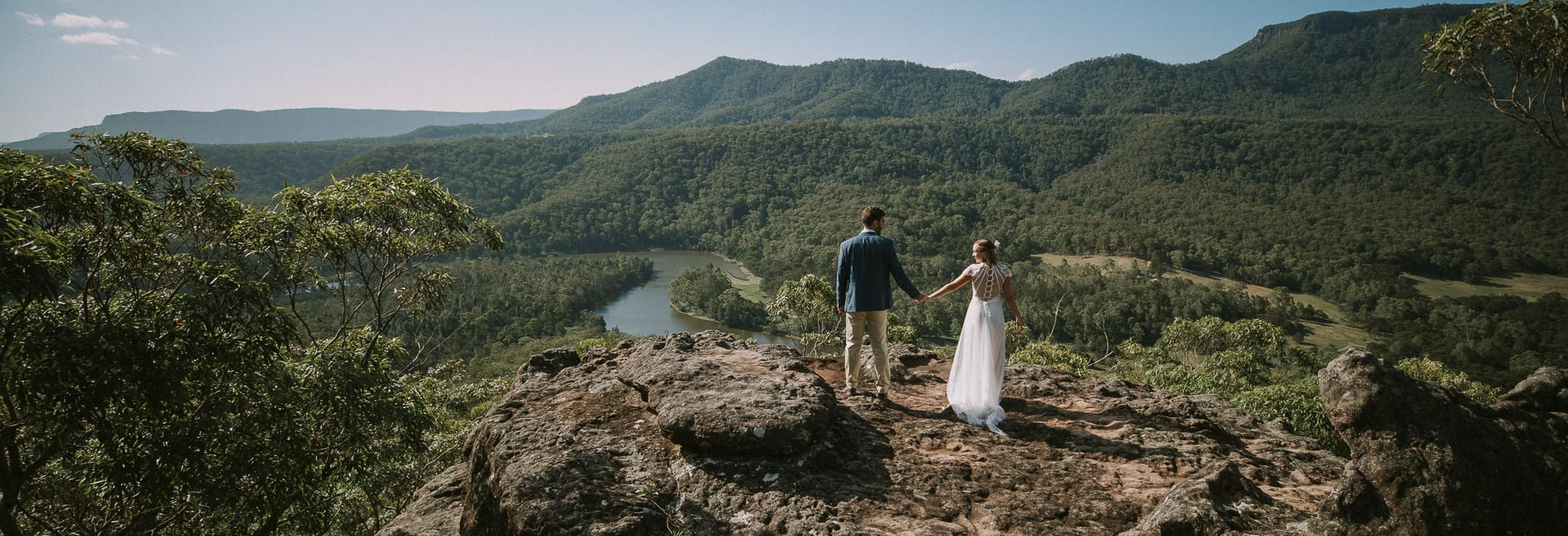 Amelia+Dan stand on the cliff face viewing the amazing view during their wedding photo shoot