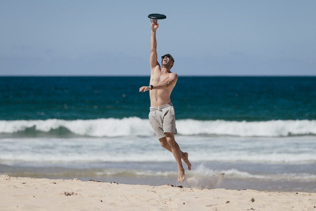 Groom catching Frisbee on the beach the morning of his wedding