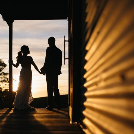 Photograph of bride and groom holding hands after their wedding and watching the sunset over Mali Brae Farm, Southern Highlands NSW.