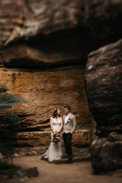 bride and groom stand below the rocks at their Kangaroo Valley Wedding; photograph with blurred vignette style finish