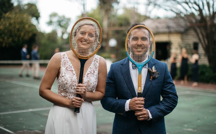 Creative wedding photography of bride and groom posing on a tennis court with old fashioned raquets over their faces in Merribee
