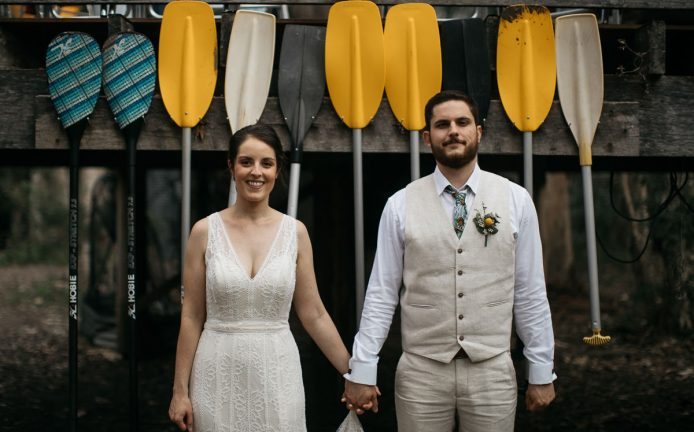 The bridal couple face the photographer smilingly, holding hands, infront of a row of colourful paddles at Paperbark Camp on the South Coast