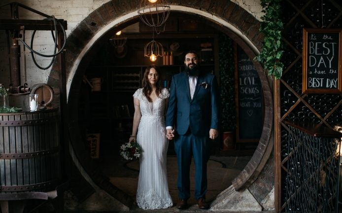 Wedding photo of a bridal couple standing in a circular doorway of their wedding venue in Bowral in the Southern Highlands