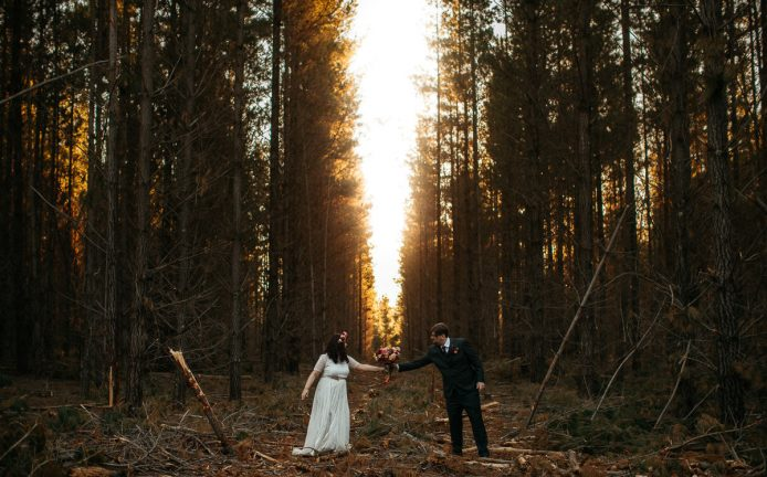 Bride hands her groom the bouquet in the forest in the Southern Highlands