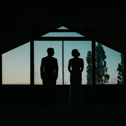 a bride and groom are silhouetted against the setting sun in a barn at a country wedding at Cooma, in the Snowy Mountains