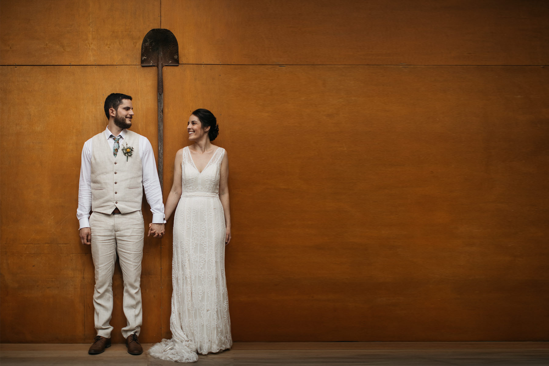Bride and groom happily hold each others hands and smile against a stylish wooden wall - Paperbark Camp Wedding Photography